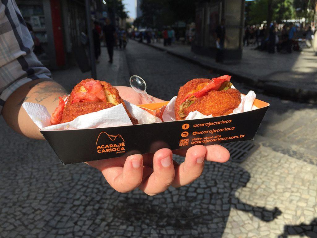 Embalagem do Foodtruck Acarajé Carioca, com duas acarajés para degustação nos eventos