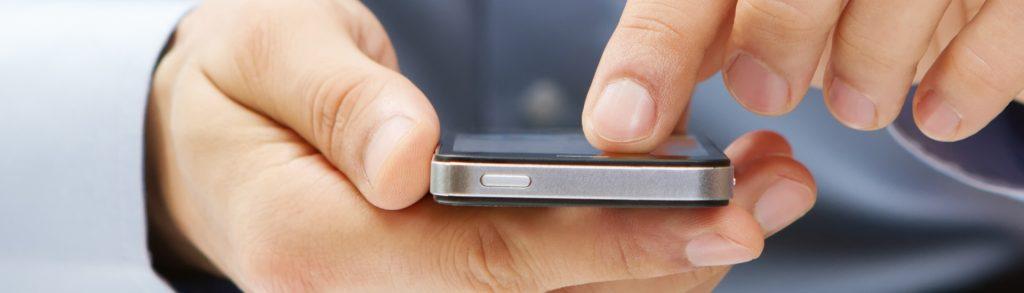 mãos segurando um smartphone com gesto de uso do aparelho, para mostrar como é importante projetar um site mobile